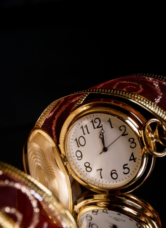 round gold watch with a tracery a red ribbon on a black background with reflection photo