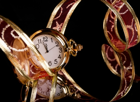 gold watch and a red delicate ribbon on a black background Stock Photo - 16271556