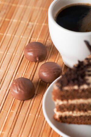 three chocolates ,a black coffee and a piece of cake Stock Photo - 17446594