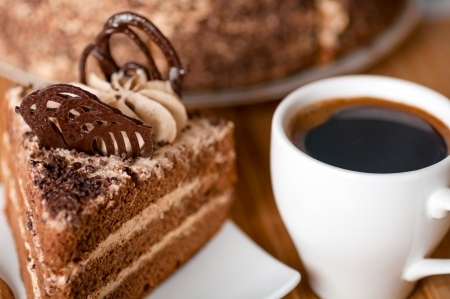 in layers: coffee ,a slice of cake on the plate on the background of cake