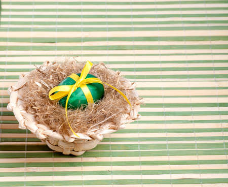 green Easter egg in a straw hat on the decorative straw Stock Photo - 17570877