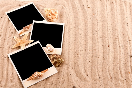 three cards lie on the sand with sand-dunes and shells photo