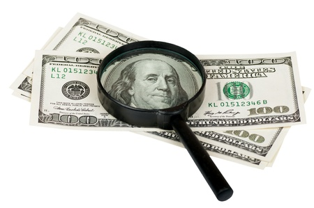 magnifying glass on the notes of a hundred dollars on white photo