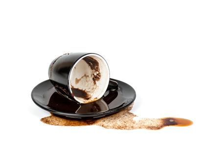 spilled coffee in inverted black Cup with a saucer isolated Фото со стока