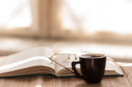 cup of coffee, standing next to an open book, on which lie glasses Stock Photo
