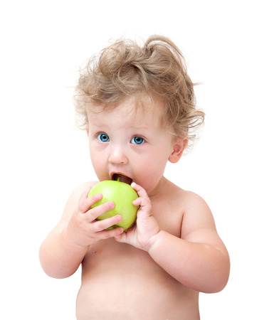 child food: baby biting a green Apple on white background