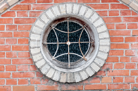 window light: round window with grille on the brick wall closeup Stock Photo