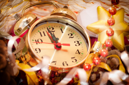12: watch hands by 12 hours and Christmas toys background closeup Stock Photo