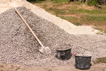 concrete construction: shovel is lying on a pile of gravel and two typed buckets Stock Photo