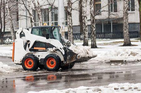 loader: loader removes snow on city streets