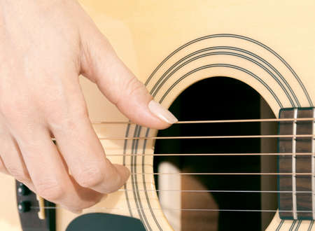 woman's hand: womans hand on the guitar strings closeup Stock Photo