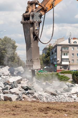 都市通りでコンクリートを粉砕する機械 写真素材