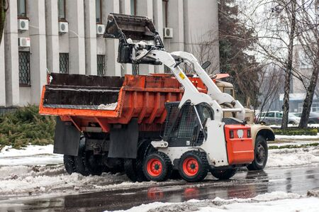 loading snow into a truck on a city street in winter