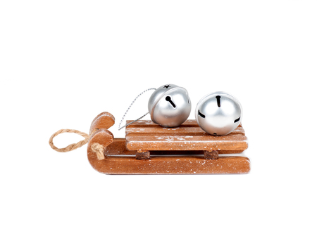silver bells lie on a wooden sleigh, isolated