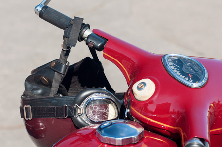 old models motorcycle, red with chrome elements, retro helmet on the steering wheel Stock Photo