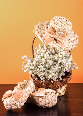 straw hat and slippers, lilies of the valley in a basket, yellow and black background