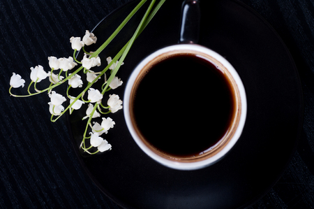 Lilies of the valley and black coffee on a black wooden background, top view, composition of black and white