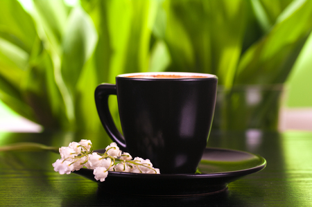 coffee in a black cup with a saucer, lilies of the valley on a saucer, green leaves background 写真素材