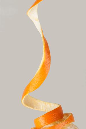 orange peel spiraling falling on a fruit on a gray background Stock Photo