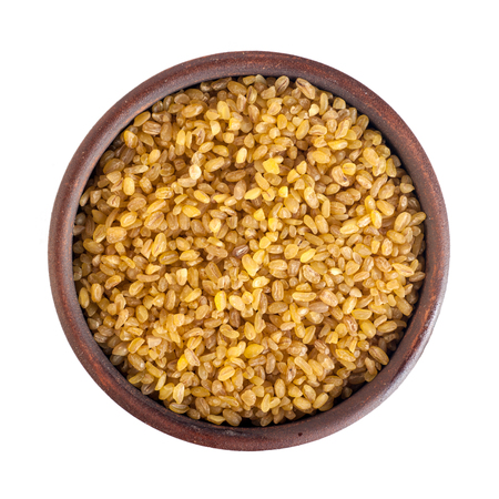 bulgur seeds, round ceramic cup, top view, isolated on white background Stock Photo