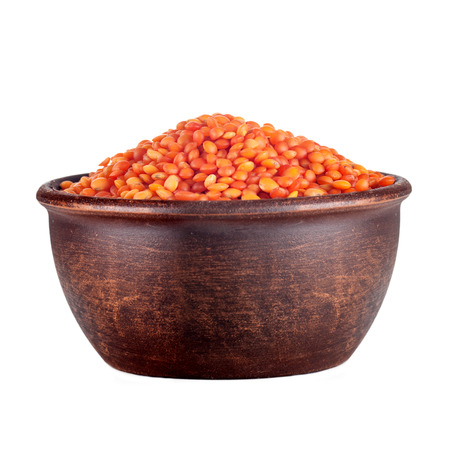 red lentil in a clay brown plate isolated on white background