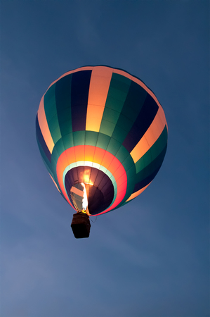 a balloon is flying in the night sky, a flame of fire inflates a balloon