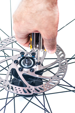 repair of bicycle wheel  brake disk close-up,isolated Фото со стока