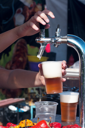 bartender pours beer into a plastic cup