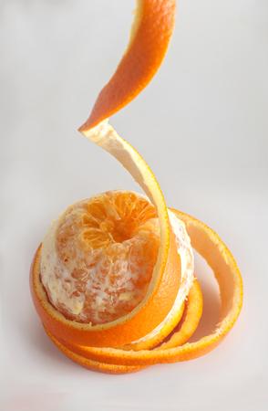 orange peel rings hanging down, on a gray background, spiral peel,