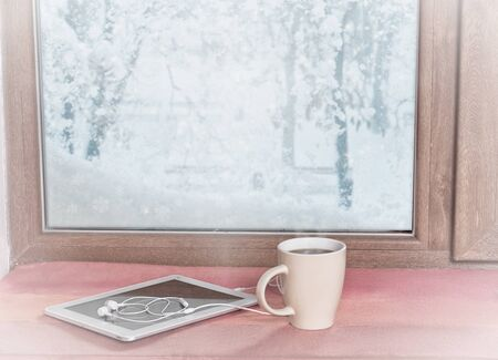 stands on the windowsill of a winter coffee window with a tablet and headphones, with a filter Stockfoto