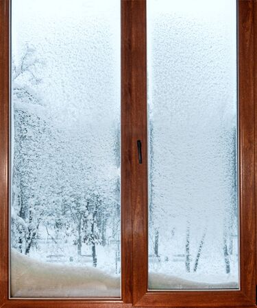 wooden window in the snow, view of snowy trees Stockfoto