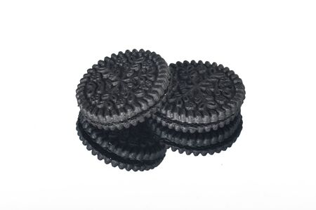 two round black cookies isolated on a white background with reflection