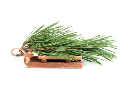 spruce branch on wooden sleigh isolated on white