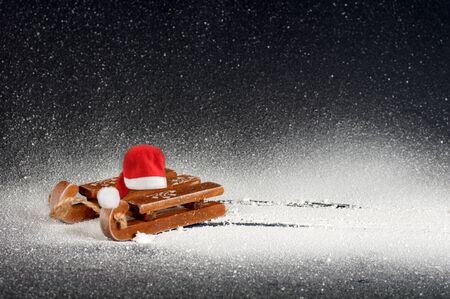 wooden sled on white snow on a black background, with a red santa hat, side view