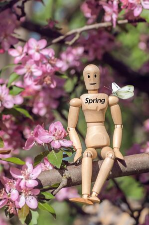 a wooden man sits on a flowering tree apple tree, red flowers of an apple tree, butterfly on the shoulder of a wooden model