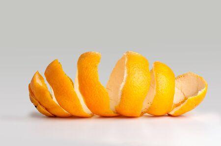 Schale einer Orangenspirale. auf der Schale drehen. auf grauem Hintergrund