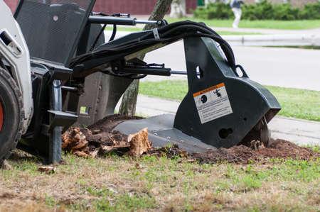machine chops a stump on the street, close-up