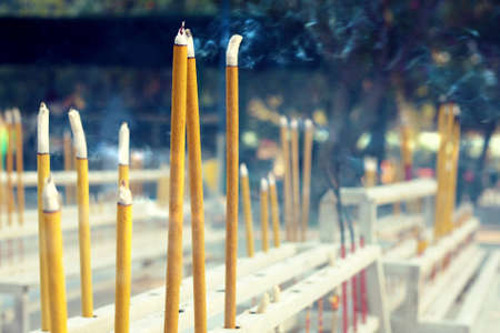 bleating: Fumigating yellow sticks in chinese temple Stock Photo