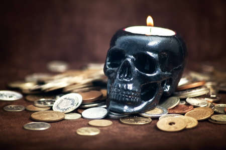 Close up skull candleholder with coins on brown background Stock Photo - 16609719