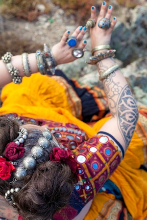 Tribal style jewelry on the hands of close-ups, iron rings and bracelets. Bright elements of decorating dancers