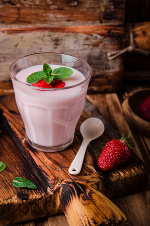 health concern: Strawberry yogurt with berries in a glass on a wooden background