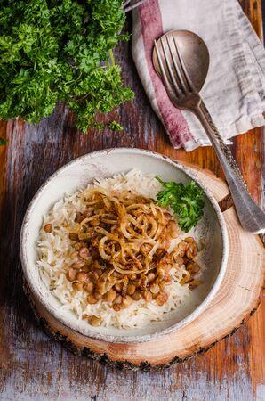 arabian food: Mujadarra - arabian dish with rice, lentils and onion on wooden background. Ramadan food. Eastern cuisine. Selective focus