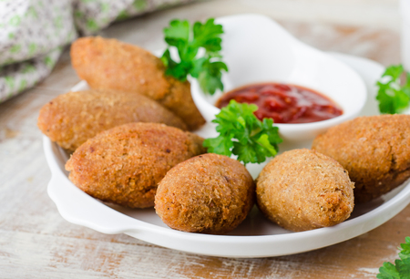 fried snack: Kibbeh - traditional Arabian meatballs, minsed meat and bulgur or rice wheat fried snack with parsley, ketchup in white plate on wooden background. Eastern cuisine.