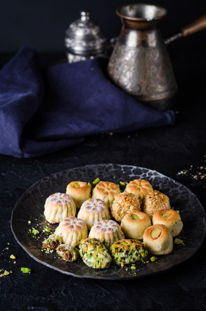 arabian food: Maamoul or mamoul - arabic cookies stuffed dates with icing cugar on vintage wooden table background. Ramadan food. Arabian sweets