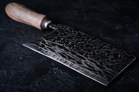 cuchillo de cocina: De época de gran cuchillo de carnicero en el fondo de piedra oscura. Foto de archivo