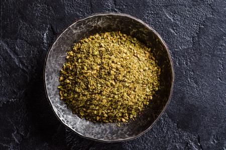 comida arabe: al este mixta especia - zaatar o zatar en un recipiente de metal de la vendimia en el fondo de piedra oscura. Foto de archivo