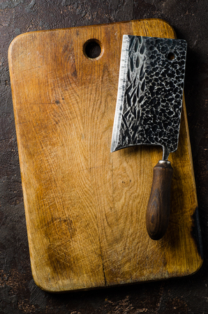 cleaver: Chopping board block and Meat cleaver large chefs knife and bowl with spice on dark background.