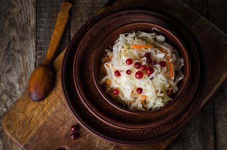 ensaladilla rusa: Sauerkraut with berries on rustic background Foto de archivo