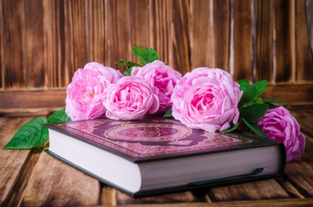 Quran with roses on wooden table. Ramadan concept