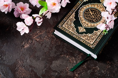 Islamic Book Koran and spring flowers brunch on dark background with arabic calligraphy that means the Holy Quran. Sring concept. Selective focus Stock Photo